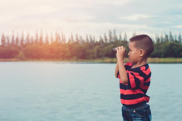 Leuke jong geitjejongen die zich op rivieroever bevindt en in kijker kijkt.