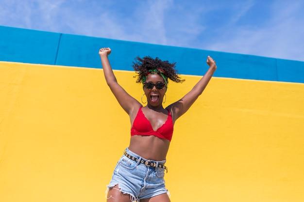Leuke jonge afro-amerikaanse vrouw lachen met opgeheven armen