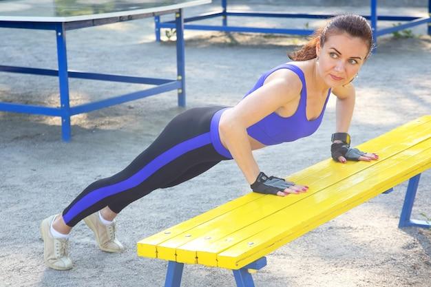 Leuke jonge atletische vrouw die gymnastiek op haar handen doet