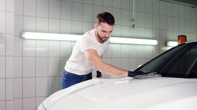 Leuke jonge automonteur veegt de auto af met een doek, bereidt zich voor op verkoop, maakt schoon
