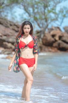 Leuke jonge aziatische vrouw in bikini gelukkig op mooi strand in de zomervakantie in thailand