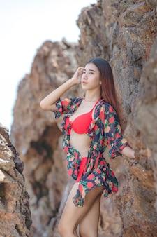 Leuke jonge aziatische vrouw in bikini gelukkig op mooi strand in zomervakantie in thailand