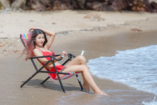 Leuke jonge aziatische vrouw in bikini op het mooie strand in de zomervakantie in thailand