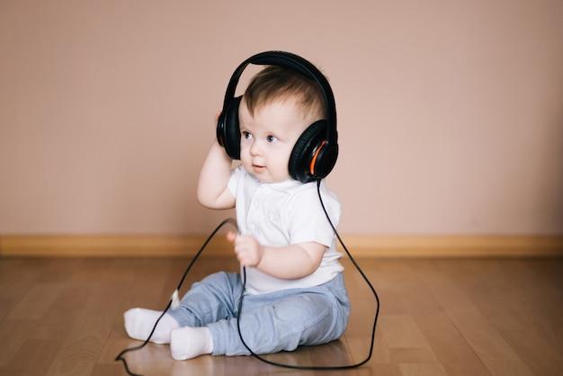 Leuke jonge babyzitting op de vloer die thuis met hoofdtelefoons speelt die aan muziek luistert