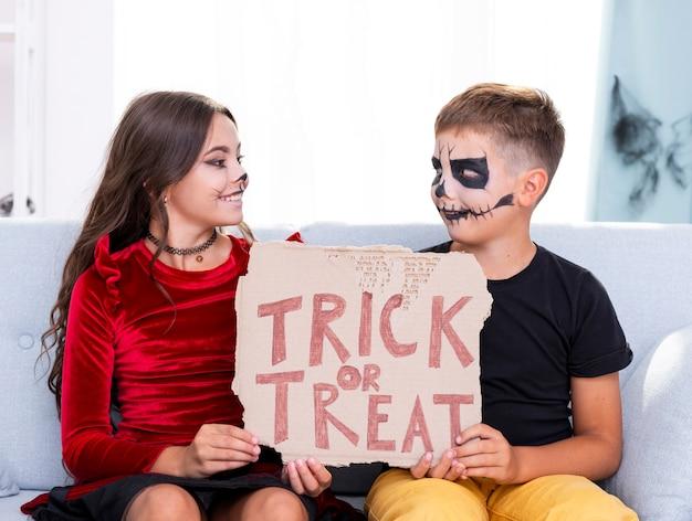 Leuke jonge broers die trick or treat-teken houden