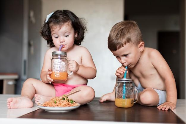 Leuke jonge broers en zussen die sap drinken