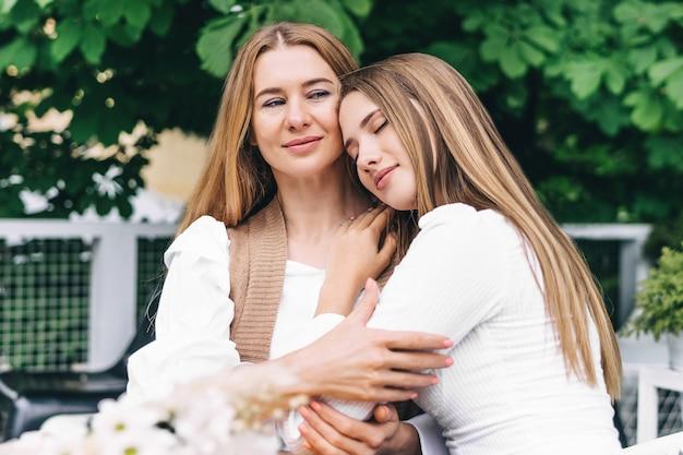 Leuke jonge dochter die haar moeder met liefde omhelst.