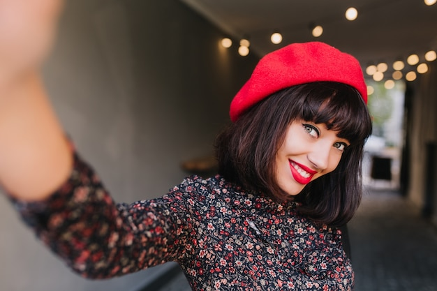 Leuke jonge franse vrouw in stijlvolle kleding vormt, verlegen glimlachend en zwaaiend met haar hand. portret van schattig brunette meisje in trendy rode hoed en retro jurk plezier binnenshuis op onscherpe achtergrond