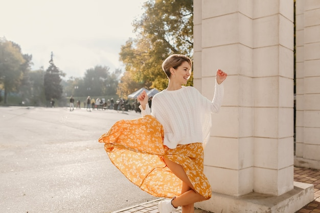 Leuke jonge gelukkig lachende vrouw in gele bedrukte jurk en gebreide witte trui op zonnige herfstdag