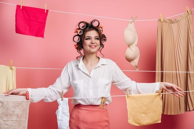 Leuke, jonge huisvrouw op een muur van touwen met kleren op een roze achtergrond