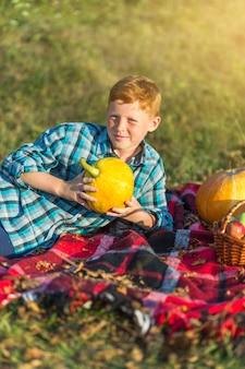 Leuke jonge jongen die een gele pompoen houdt