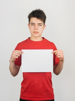 Leuke jonge jongen die in rode t-shirt een ruimtedocument exemplaar houdt