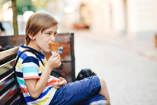 Leuke jonge jongen die roomijs eet. jongen zittend op de bank buiten. weekend zomerdag. kind genieten van lekker ijs in knapperige kegel. zomervakantie, lifestyle en mode-concept.