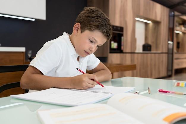 Leuke jonge jongen die zijn huiswerk doet