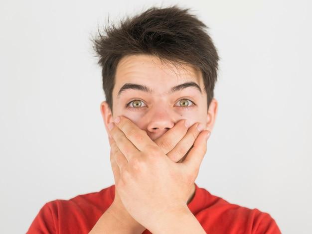 Leuke jonge jongen in rode t-shirt die tot zwijgen wordt gebracht