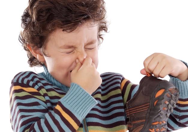 Leuke jonge jongen met stinkende schoen pitching zijn neus