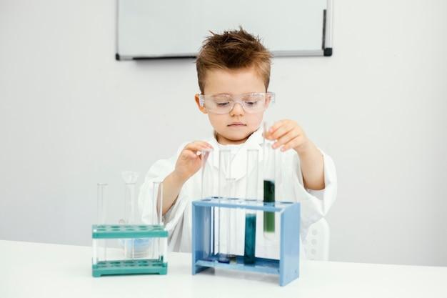 Leuke jonge jongenswetenschapper die experimenten in het laboratorium met reageerbuizen doet