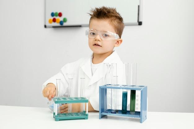 Leuke jonge jongenswetenschapper die experimenten in laboratoriumjas doet