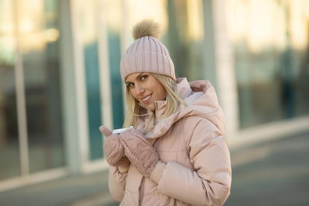 Leuke jonge kaukasische tienervrouw in beige hoed met pompon en roze wanten die dampende kop hete thee of koffie houden, openlucht in zonnige de winterdag.