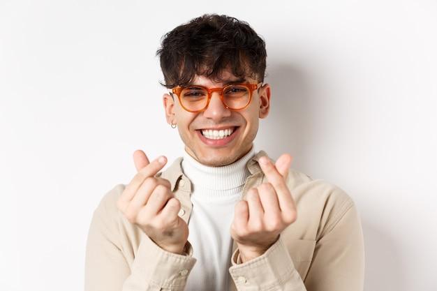Leuke jonge kerel in glazen die en vingerharten glimlachen tonen, die zich op witte muur bevinden.