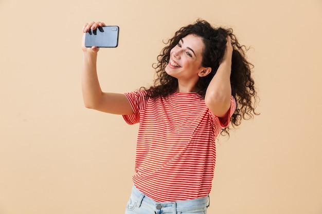 Leuke jonge krullende vrouw maken selfie praten via de mobiele telefoon.