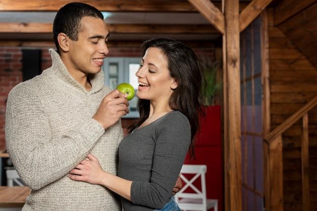 Leuke jonge man en vrouw die een appel hebben