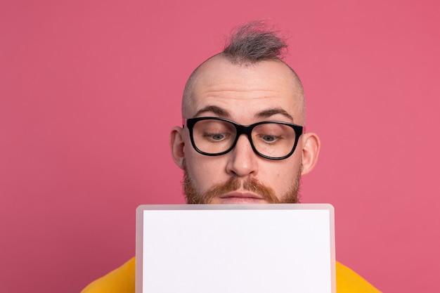 Leuke jonge man kijkt uit ogen wit leeg leeg reclamebord voor promotionele inhoud geïsoleerd studio-opname
