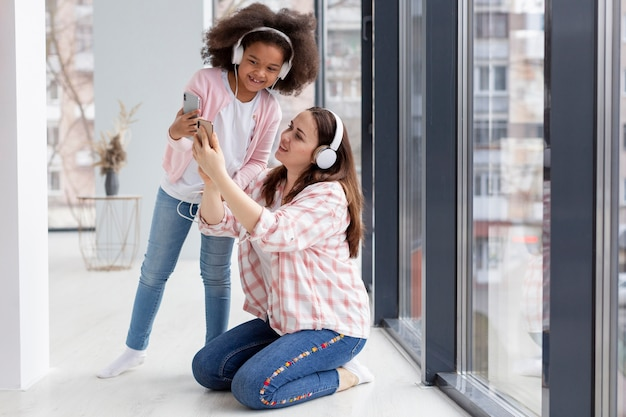 Leuke jonge meisje en moeder die aan muziek thuis luisteren