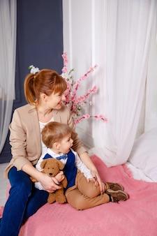 Leuke jonge moeder koestert haar zoontje in bed. moeder zorgt 's avonds voor het kind. mama en zoon rusten thuis in bed. gelukkige moeder en haar kleine kind die verhaaltje voor het slapengaan thuis lezen. slaap zacht