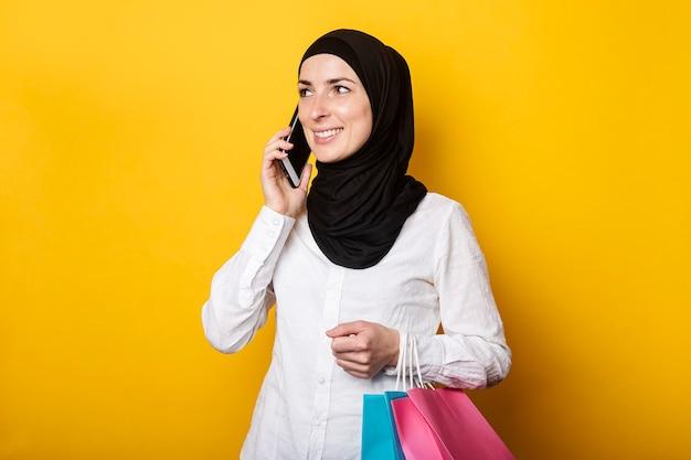 Leuke jonge moslimvrouw in hijab boodschappentassen houden en praten aan de telefoon op geel
