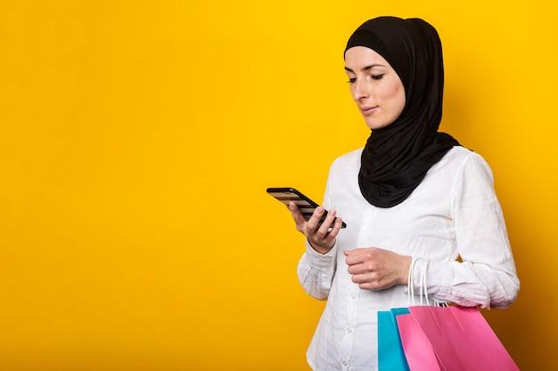 Leuke jonge moslimvrouw in hijab houdt boodschappentassen en gebruikt telefoon om te bestellen op geel