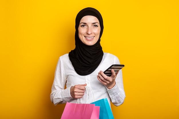 Leuke jonge moslimvrouw in hijab houdt telefoon en boodschappentassen op geel