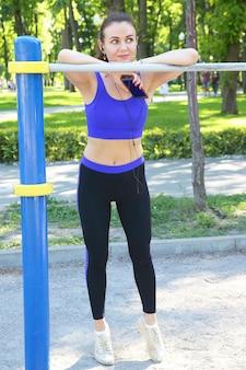 Leuke jonge sportieve vrouw, luisteren naar muziek tijdens een wandeling