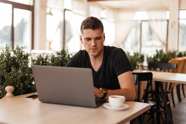 Leuke jonge succesvolle man in een trendy zwart t-shirt met een laptop zit aan een tafel in een café en werkt aan een interessant creatief project op internet. freelancer.