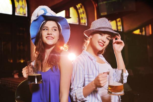 Leuke jonge vriendinnen in beierse hoeden glimlachen aan de bar