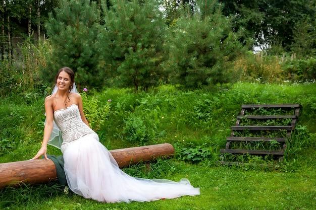Leuke jonge vrouw bruid in jurk wandelen in land dorpshuis buiten op trouwdag. gelukkige bruid op woensdag in luxe park of bos. concept van huwelijksdag en getrouwd. ruimte voor site kopiëren