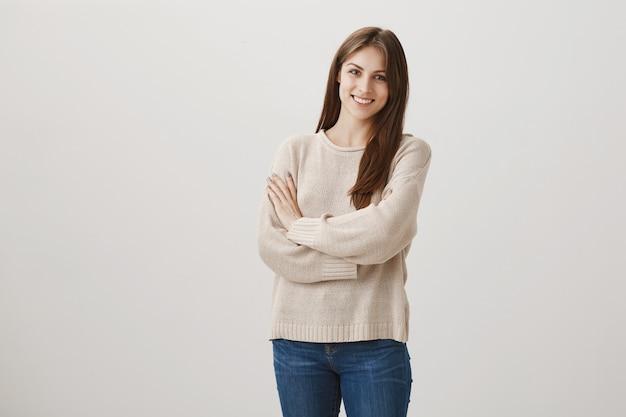 Leuke jonge vrouw die bij camera op grijs glimlacht