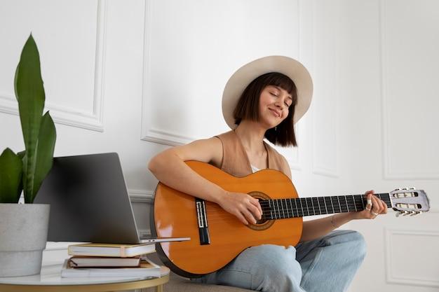 Leuke jonge vrouw die binnen gitaar speelt