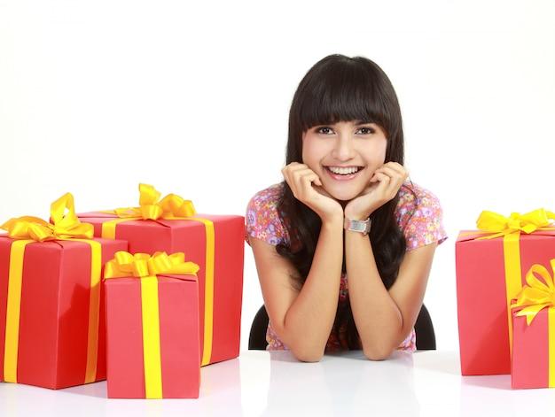 Leuke jonge vrouw die door geïsoleerde pakketten wordt omringd
