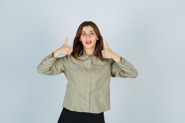 Leuke jonge vrouw die dubbele duimen in shirt, rok toont en zich afvraagt, vooraanzicht.