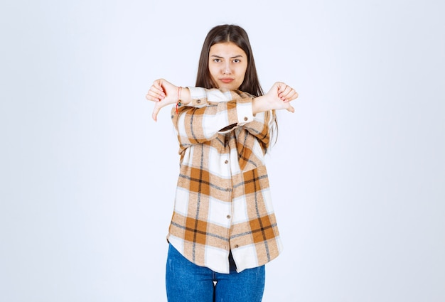 Leuke jonge vrouw die duimen neer op witte muur geeft.