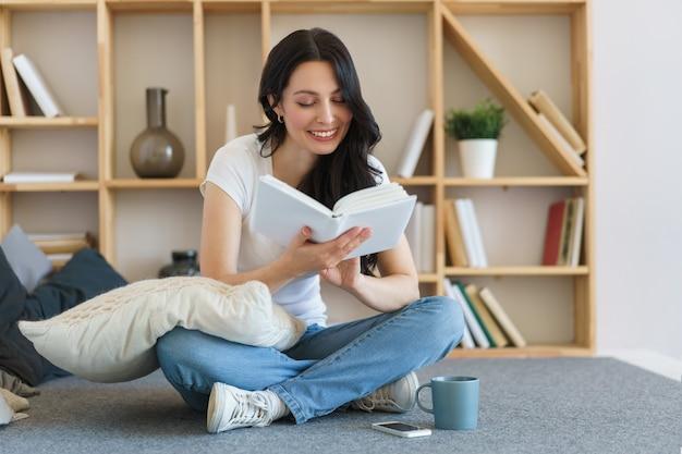 Leuke jonge vrouw die een boek leest terwijl om thuis in een weekend te zitten.