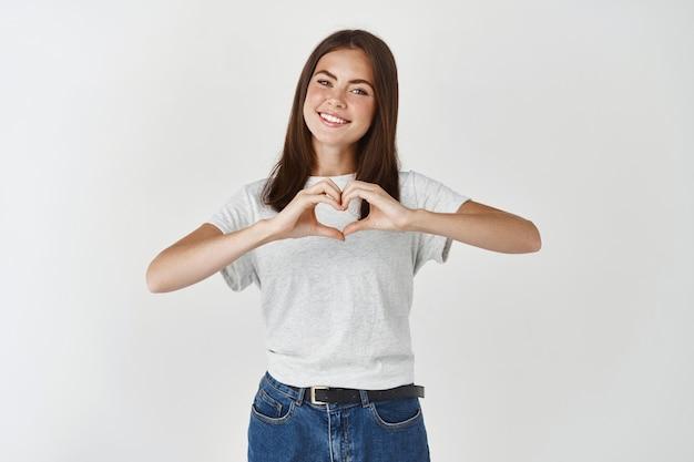Leuke jonge vrouw die een hartteken toont, ik hou van je gebaar, ik wens een gelukkige valentijnsdag, staande over een witte muur.