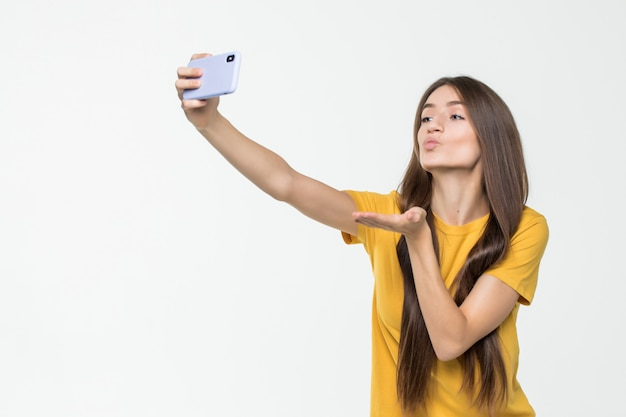 Leuke jonge vrouw die een selfie nemen en lucht-kus geven die op witte muur wordt geïsoleerd