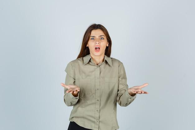Leuke jonge vrouw die een vraaggebaar in overhemd maakt en er verbaasd uitziet. vooraanzicht.