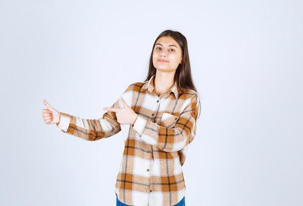 Leuke jonge vrouw die gebaren op witte muur doet.