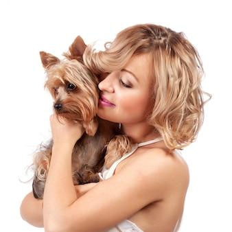 Leuke jonge vrouw die haar hond knuffelt
