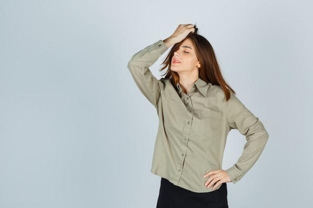 Leuke jonge vrouw die haar terug kamt in shirt, rok en er ontspannen uitziet, vooraanzicht.