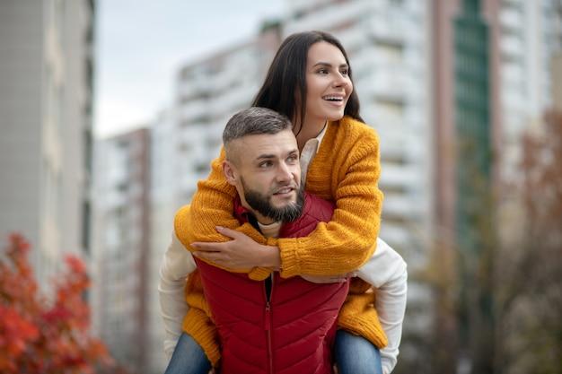 Leuke jonge vrouw die haar vriend vasthoudt terwijl hij door hem wordt vastgehouden