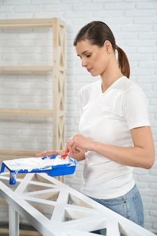 Leuke jonge vrouw die houten rek schildert